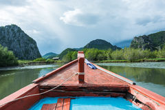 Front view of row boat on stream going to the moutain. Stock Photo