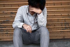 Front view of Sad depressed young Asian business man covering face with hands. Front view of Sad depressed young Asian business man covering face with hands Stock Photos