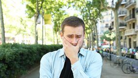 Sad and frustrated man looking at camera in the street stock footage