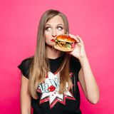 Sadly girl thinking eating tasty humburger or no. Front view of sadly young girl looking at side and thinking eating tasty humburger or no. Pretty woman wearing royalty free stock photography