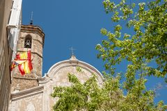 Front view of san marti church in the small catalan town of Sant Celoni on a sunny summer day with trees and spanish flags and stock photos