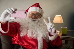 Front view of Santa Claus sitting in sofa at home Using cell phone for communication and leisure. Taking a photograph. Front view of Santa Claus or Father royalty free stock photos