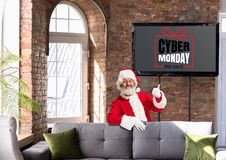 Front view of Santa pointing of screen with cyber monday lettering in modern home or office
