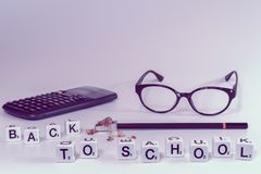 Front view of school supplies with scrabble letters spelling the words back to school in girly pink color tones. Concept of college student, university stock photo