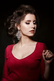 Front view of seductive brunette girl wearing red dress and big earrings. Woman with perfect make up and stylish haircut posing in Stock Images