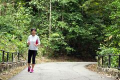 Front view of senior woman jogging through park Stock Photography