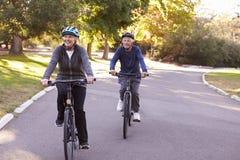 Front View Of Senior Couple que completa un ciclo a través de parque junto Imagen de archivo