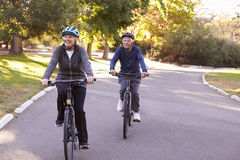 Front View Of Senior Couple som cyklar parkerar igenom, tillsammans fotografering för bildbyråer