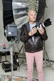 Front view of senior man with camera in photographer's studio royalty free stock image