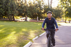 Front View Of Senior Man Cycling Through Park Stock Photo