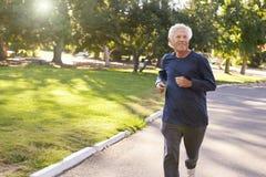 Front View Of Senior Man som joggar parkerar igenom royaltyfria bilder