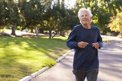 Front View Of Senior Man som joggar parkerar igenom Arkivfoto