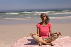 Senior woman with eyes closed doing yoga the beach. Front view of senior woman with eyes closed doing yoga on beach in the sunshine royalty free stock image