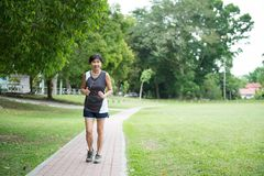 Front view of senior woman jogging through park Stock Photos