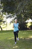 Senior woman jogging through park. Front view of senior woman jogging through park stock photography