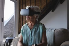 Senior woman using virtual reality headset. Front view of a senior woman using virtual reality headset in living room at home stock photos