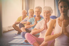 Front view of seniors relaxing with fitness instructor Royalty Free Stock Photos