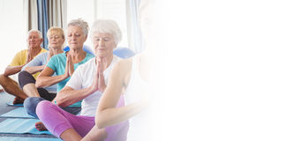 Front view of seniors relaxing with fitness instructor Royalty Free Stock Images