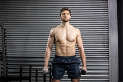 Front view of serious man lifting weight Stock Photos