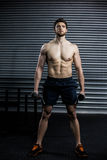 Front view of serious man lifting weight Royalty Free Stock Image