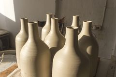 Front view shot for batch of traditional handmade bottle design from gray colour raw ceramic material after cooked at sunset time royalty free stock images