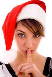 Front view of shushing woman in christmas hat Royalty Free Stock Image