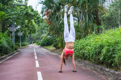 Front view of slim fit young woman practicing yoga doing straight handstand on park path  summer day. Sporty girl Stock Photo