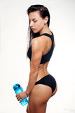 Front view of slim fitness woman drinking water. Full body length portrait  over white background Royalty Free Stock Photos