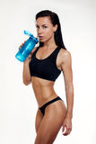 Front view of slim fitness woman drinking water. Royalty Free Stock Images
