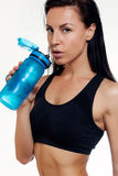 Front view of slim fitness woman drinking water. Full body length portrait  over white background Stock Image