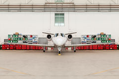 Front View of Small Airplane in Hangar. Front Nose View of Small Passenger or Cargo Airplane in Bright Hangar with Various Bins and Storage in Background Stock Photo