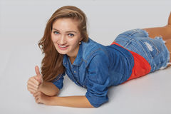 Front view of smiling beautiful woman lying on the floor over gr Stock Photo
