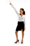 Front view of smiling businesswoman pointing up Stock Images