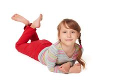 Front view of smiling child girl lying on floor. Front view of smiling child girl lying on stomach on the floor looking at camera smiling, over white background Stock Images