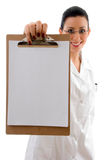 Front view of smiling doctor showing writing pad. With white background Royalty Free Stock Images