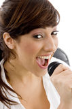 Front view of smiling female singing on microphone Stock Photo