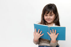 Front view of smiling little girl reading a book stock photo