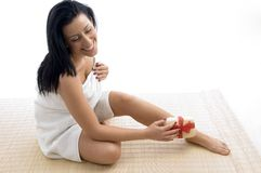 Front view of smiling woman scrubbing her legs Stock Photos