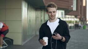 Front view of smiling young man with smartphone and coffee listening to music stock video