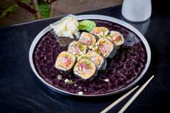 Front view on spicy roll with tuna orsalmon. Suchi. japanese food style. Seafood. Healthy, balanced, dieting meal. sushi rolls set. On dark plate. Copy space royalty free stock image