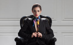 Front view of strict business woman in black suit sitting in bos Stock Photography