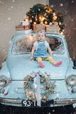 Front view of sweet and fashionable little cute girl sitting on blue retro car decorated for Christmas.