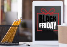 Front view of tablet and office accessories with black friday lettering on blurred background