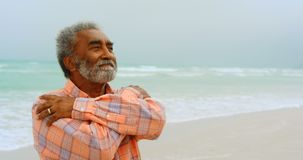 Front view of thoughtful active senior African American man shivering on the beach 4k stock video footage