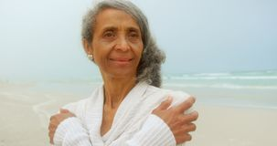 Front view of thoughtful active senior African American woman shivering on the beach 4k. Front view of thoughtful active senior African American woman shivering stock footage