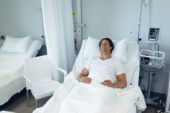 Male patient relaxing on bed in the ward at hospital. Front view of thoughtful Caucasian male patient relaxing on bed in the ward at hospital stock images