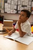 Thoughtful schoolboy studying at desk in a classroom. Front view of thoughtful mixed-race schoolboy studying at desk in a classroom at elementary school stock photo