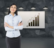 Front view of a thoughtful woman with crossed hands. Increasing bar chart and an arrow on the whiteboard. Stock Photo