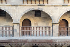 Front view of three arches with interleaved wooden balustrades. At the arcade surrounding the courtyard of caravansary Wikala of Bazaraa, Medieval Cairo, Egypt Stock Photo