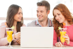 Front view of three students using laptop. Stock Image